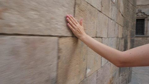 Woman hand gently stroke surface, slide on stony wall of old building at Gothic Quarter of Barcelona. Closeup shot of female palm, tourist lady walk along construction made from stone brick