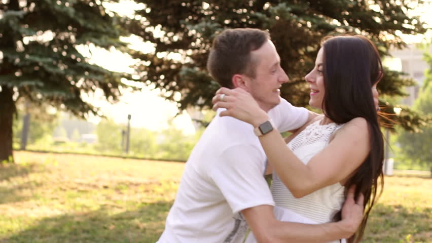 A merry couple in love rejoices and fools around in the summer park, they fall on the grass and laugh. Slow motion. | Shutterstock HD Video #1017484747