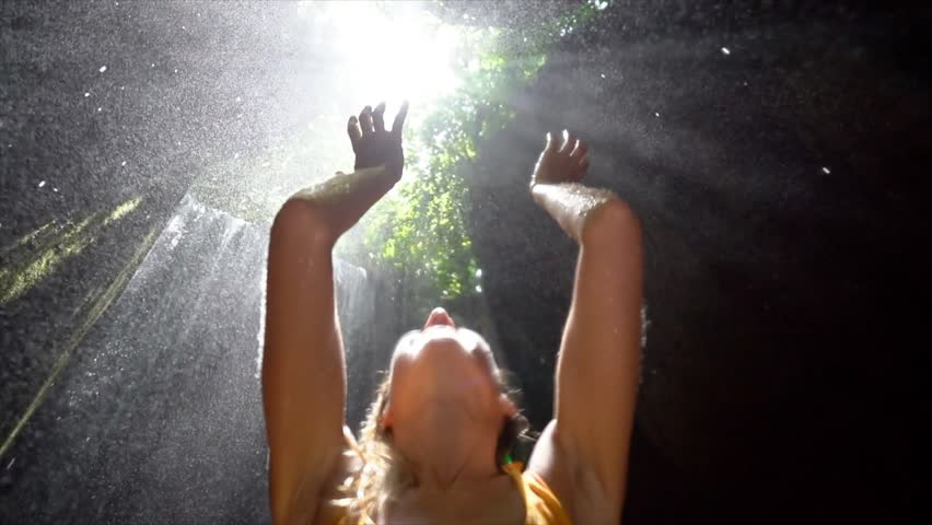 Young woman in tropical rainforest looking up at beautiful light and touching the rain drops with hands. People travel enjoying nature and life concept. Slow motion video
