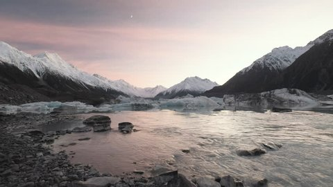 Sunset at Tasman Lake on New Zealand's South Island with a glacial lake surrounded by snow capped mountains