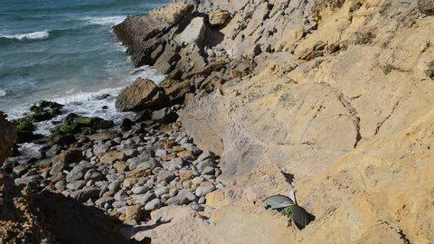 Tent set up along rocky coastline of Portugal near Guincho beach.