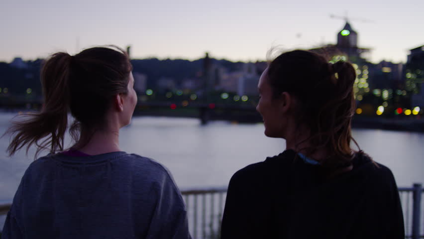 Tracking Shot Of Friends Walking Down Spiral Ramp, At Sun Down, City Lights Across River In Background, Slow Motion | Shutterstock HD Video #1017571177