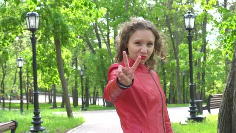 Victory Sign by Successful Female Designer in Red Leather Jacket, Portrait at Green Park.