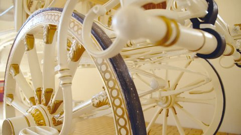 Big wheels on white baroque style horse carriage close-up 4K. Dolly slide shot of wheels in focus decorated with gold details.