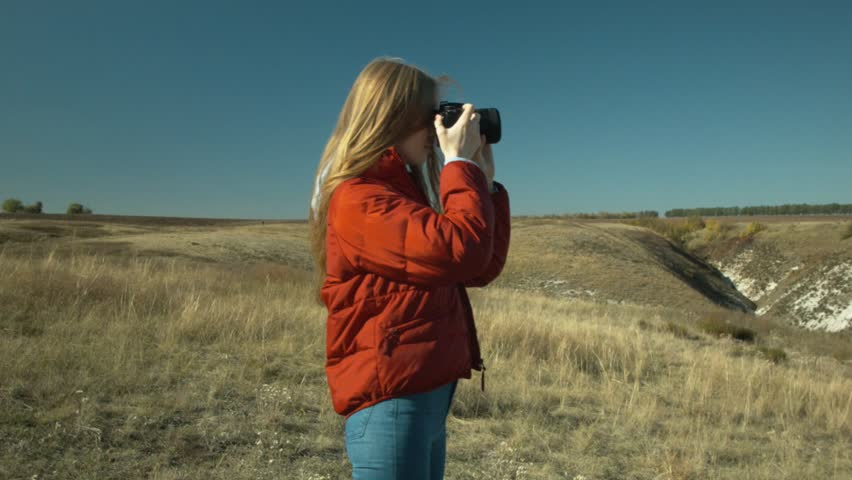 Young beautiful girl makes photos of the surrounding landscape. Girl you are a hill. Sunny day. Rest and travel. | Shutterstock HD Video #1017647977
