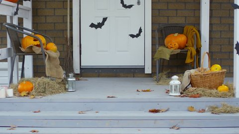 Happy little boy and girl dressed like witch and skeleton sitting on porch decorated for Halloween, holding jack-o-lanterns, playing and laughing