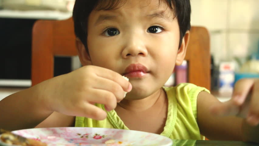 Thai child eating food on the table   Shutterstock HD Video #1017689287