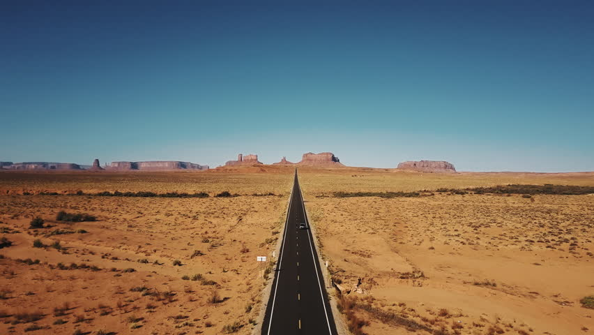 Drone follows silver car driving along famous sunny American desert highway road in Monuments Valley in Arizona and Utah
