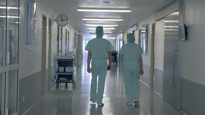 People in a clinic building. Man and woman walking through an empty hallway in hospital. | Shutterstock HD Video #1017757147