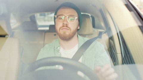 Portrait of Stylish Young Man Drives Car through big Sunny City. Camera Shot Made From the Front Windshield.