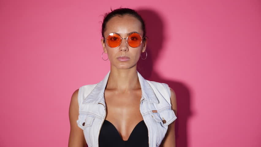 Closeup portrait of adorable woman. Girl dressed in summer hipster clothes and sunglasses. Model posing on camera with lovely smile, isolated over pink background. 4k. Slow motion #1017799987
