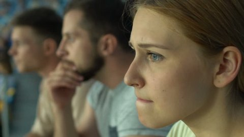 Girl fan with friends watching sport game or races at stadium, worried, anxious