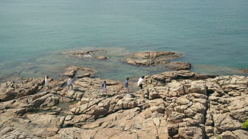 Group of five young asian adults walking on rocks by the sea. | Shutterstock HD Video #1017810247