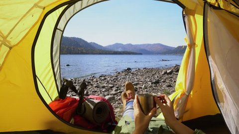 Camping woman lying in tent Close up of Girl feet wearing hiking boots relaxing on vacation POV.