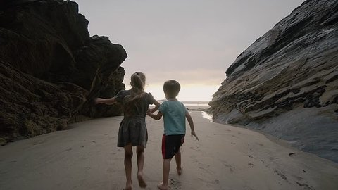 Kids exploring the beaches of Newquay Coast around Cornwall South West England UK