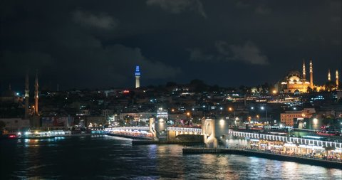 Timelapse shot of night Istanbul - view at the Golden Horn gulf full of ferry boats, Galata Bridge and Suleymaniye Mosque with beautiful backight. 4k video