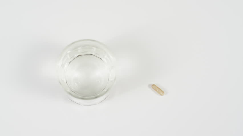 High angle view of a hand taking a glass of water and a pill. | Shutterstock HD Video #1017860947