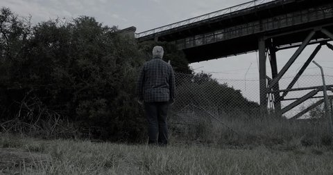 Creepy man wearing white halloween mask turns then stands with head tilted in scary manner then walks slowly away in front of bushes and old railway bridge