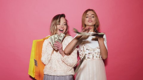 Two young stylish smiling blond women holding shopping bags and making rain money. Hot girls dressed in summer hipster clothes and throwing bills out of a bundle money. Posing on pink background