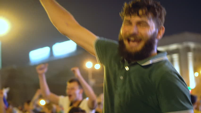 Guy in green T-shirt rejoices at street party in the night city winning football. Atmospheric celebration in honor of victory. Guy goes into crowd jump and rejoices with crowd victory of Russia