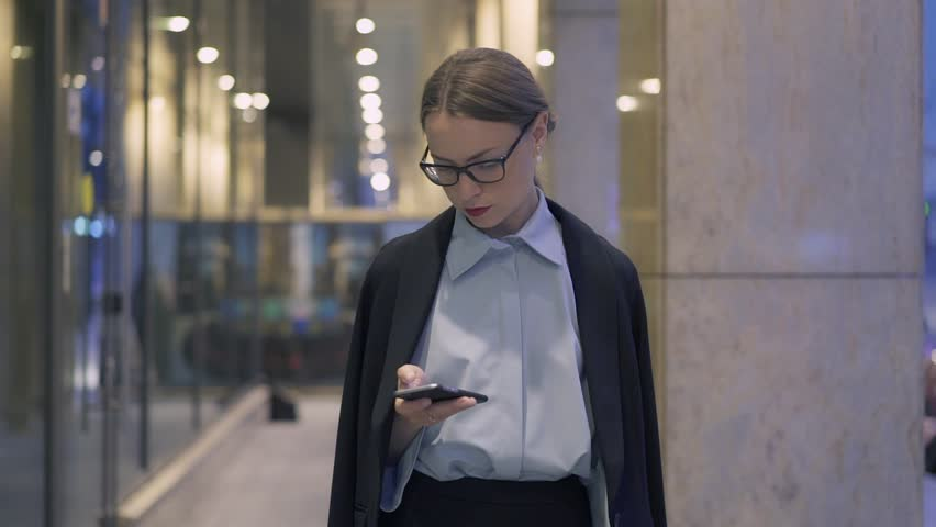 Serous young businesswoman wearing glasses and suit walking in evening city and web surfing on her smartphone. Tracking slow motion medium shot | Shutterstock HD Video #1017963847