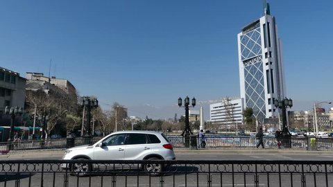 SANTIAGO, CHILE - Sep 11 2018. Scene of light traffic on the Pio Nono bridge is cut by a tourist bus covering the screen. View of the Telephone Tower, Andes mountains, Plaza Italia Obelisk and Mapocho