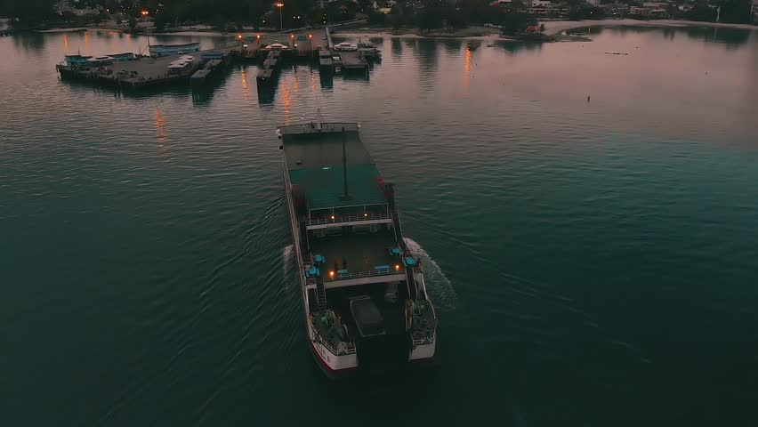 The ferry enters the port off the coast after sunset. The ferry boat delivers passengers and transport to the pier on the island | Shutterstock HD Video #1017998437