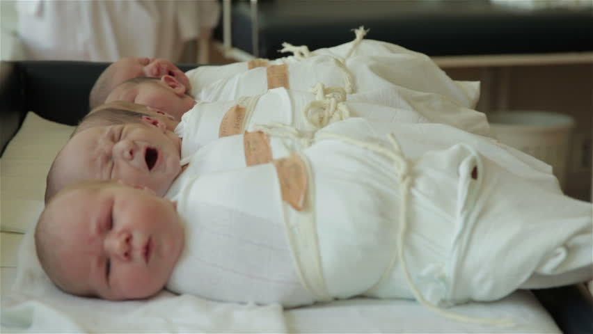 Newborn babies lying on table in maternity ward. Hungry baby old two days crying and other babies sleeping. Face expressions. Beautiful infants. Shallow depth of field, childcare, child, kid. 30 fps.