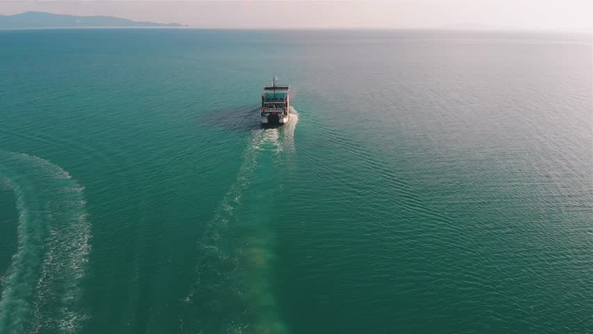 Above the ferry going on the sea. The ferry boat carries passengers and transport along the green sea | Shutterstock HD Video #1018000927
