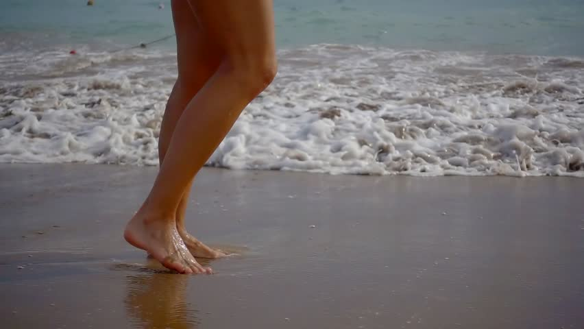 Close-up view of naked slim legs of woman walking in a seacoast over big waves | Shutterstock HD Video #1018003297
