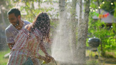 Happy Young Couple Has Fun on a Hot Summer Day Playing with Water Hose Sprinkler in the Garden. Two Young People in Love Got Wet Jokingly Fighting with Hose. In Slow Motion.