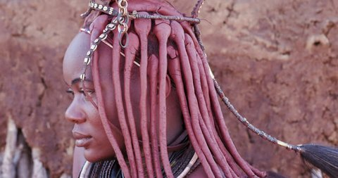 4K close-up tilt up view of a pretty Himba girl showing head gear and neck jewellery,Namibia