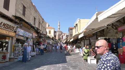 Rhodes, Greece - September 26, 2018: Locals and tourists at the narrow street leading to the old Suleymaniye Mosque by the town square of Rhodes with shops on both sides.