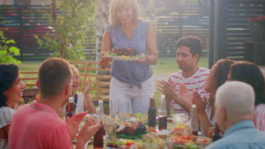 At the Family Garden Party, Mother Brings Dish with Roasted Bird to the Table. Family and Friends Gathered together at the Big Table. Eating, Drinking and Having Fun. | Shutterstock HD Video #1018050757