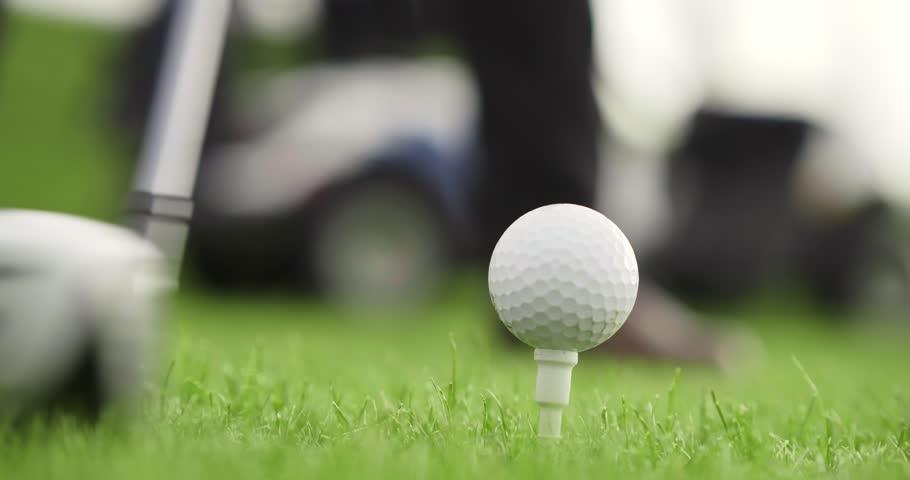 Golf player hitting golf ball. Close up of brassie kicking golf ball