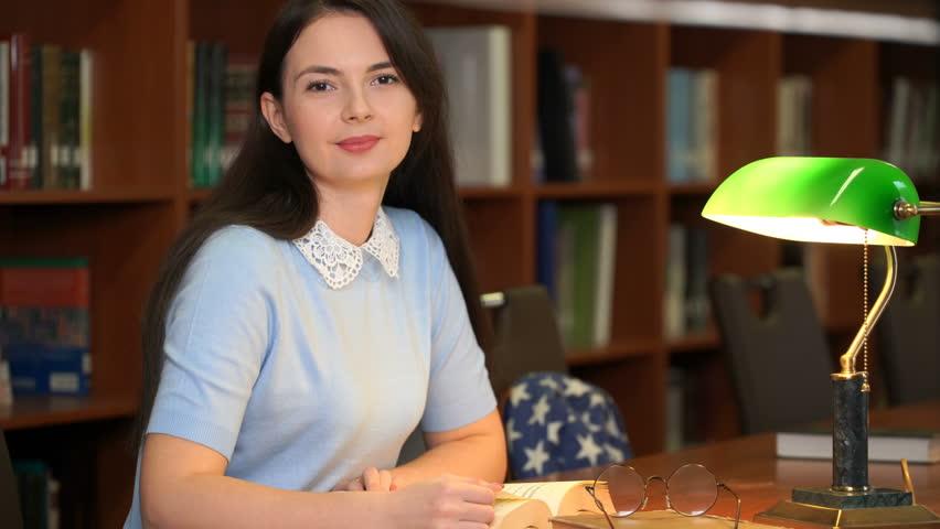 Footage portrait of schoolgirl doing their homework in library. Pretty woman read book in library office. 4k education video | Shutterstock HD Video #1018086427