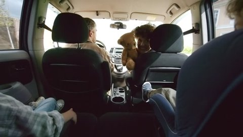 Shot from inside of moving car: happy young mother holding plush toy and playing with unrecognizable preschool-age boy in child seat and his elder sister riding in backseat on family road trip