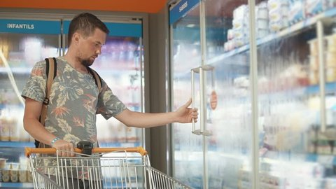 Casual guy with shopping cart choosing food in a grocery store. Man taking frozen yogurt out of freezer, tasty dessert.