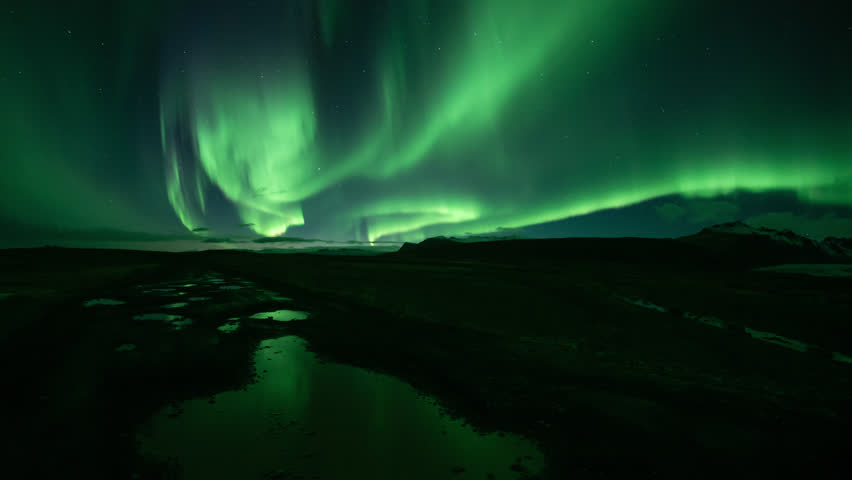 Bright realistic Aurora Borealis over mountains, reflecting in puddles, Skaftafell Iceland.mov