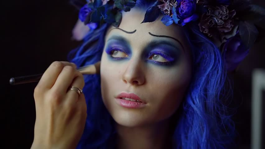 Close-up portrait of a beautiful girl with fantastic blue makeup, long colored eyelashes. the hand of the make-up artist puts a tone on the cheek with a brush. | Shutterstock HD Video #1018171747
