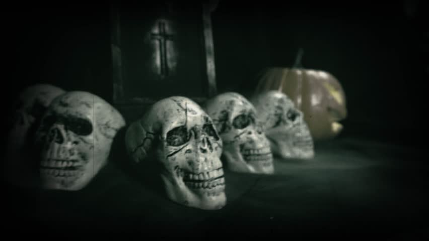 Old film look of halloween set decoration with skulls, grave and jack o'lantern   Shutterstock HD Video #1018184707