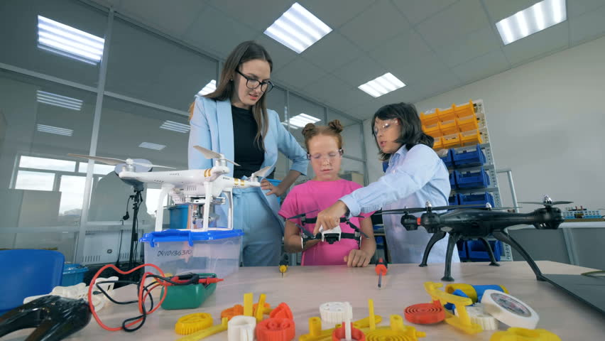Female researcher and two school children are exploring drones. Innovation in education concept. | Shutterstock HD Video #1018188397