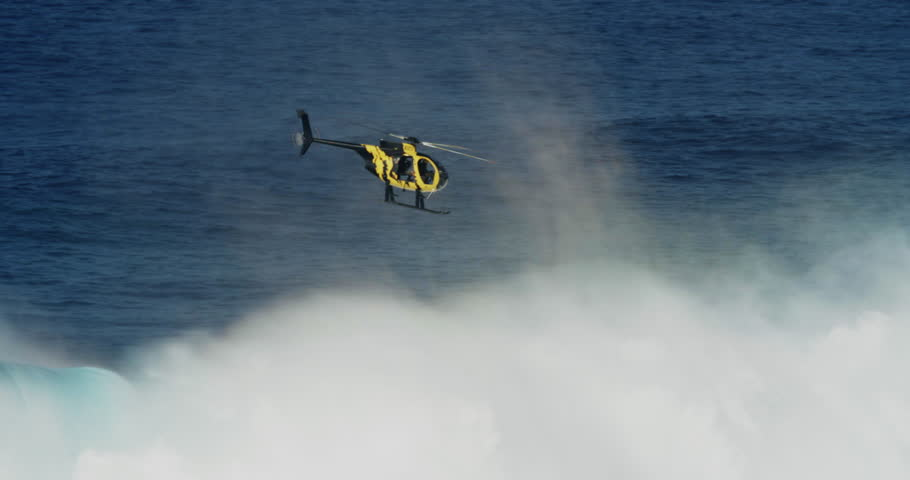 Cinema helicopter filming large surf in Maui during big wave session #1018195357