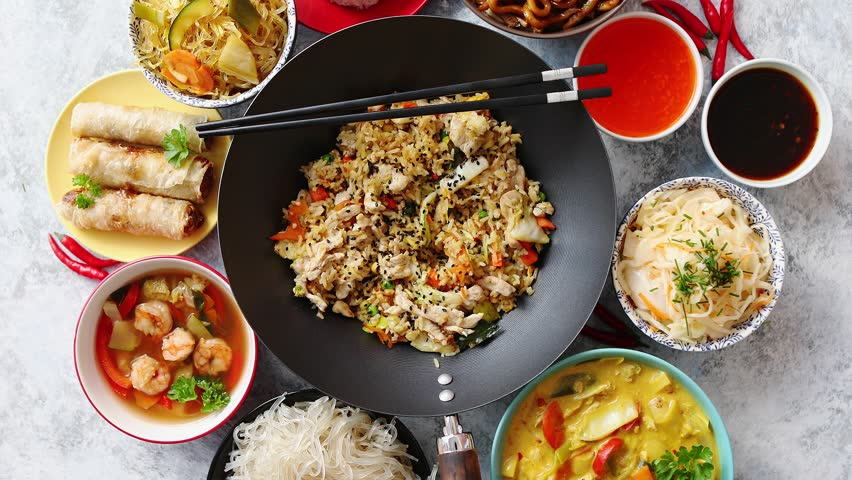 Chinese food set. Chinese noodles, fried rice with chicken, tom yum soup, spring rolls, deep fried fish and udon. Top view. Asian style food concept composition. | Shutterstock HD Video #1018208107