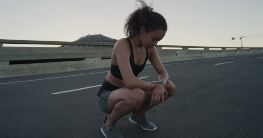 Attractive hispanic woman runner resting exhausted after intense running workout training cardio athletic female sportswoman in city at sunrise close up | Shutterstock HD Video #1018213927