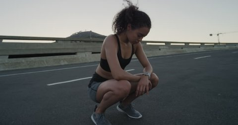 attractive hispanic woman runner resting exhausted after intense running workout training cardio athletic female sportswoman in city at sunrise close up