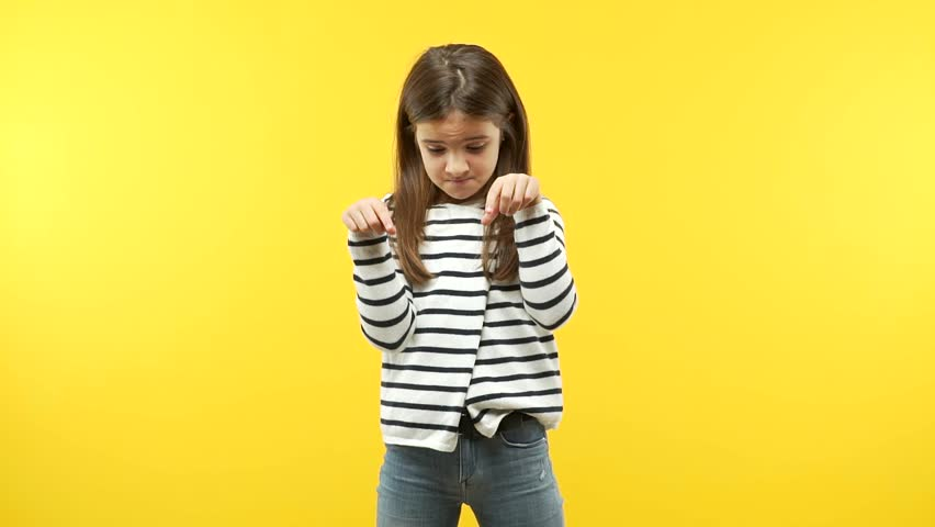 Funny child girl against an orange background pointing down ...