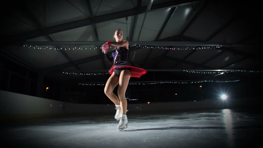 An elegant figure skater is having a beautiful performance in the ice rink. | Shutterstock HD Video #1018348387