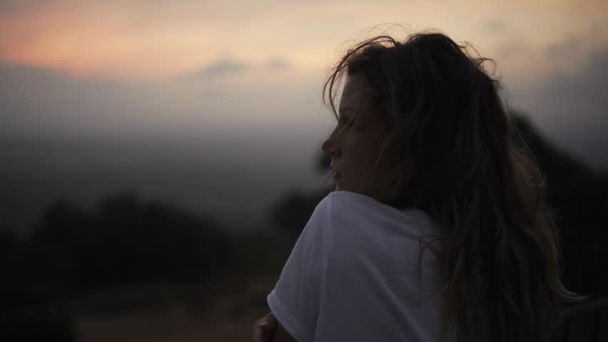 Woman on high mountain at dusk after sunset in Santuari de Cura in Mallorca, Spain