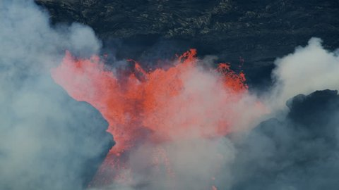 Aerial view fountains of boiling red hot magma shooting skywards from fissures in the earths crust with lava rock cooling and solidifying Hawaii USA RED WEAPON